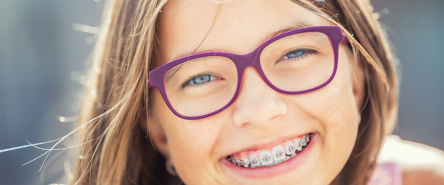 Girl with braces and glasses smiling