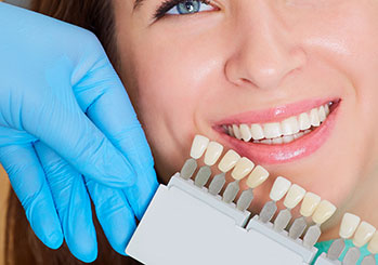 Woman smiling next to a teeth whitening